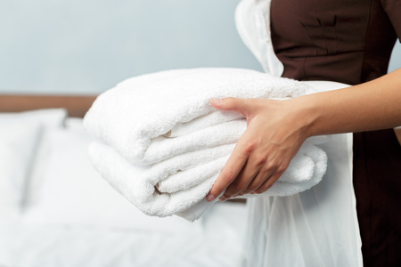 Maid with fresh clean towels during housekeeping in a hotel room Stock Photo