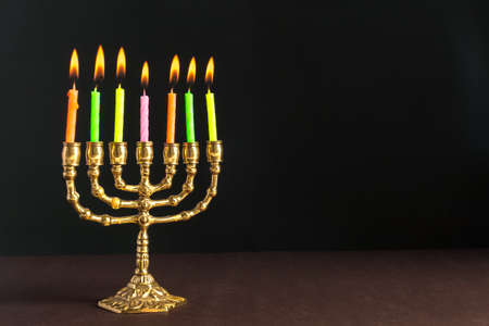 Bronze Hanukkah menorah with burning candles Imagens