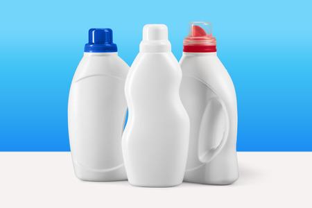 Envases de plástico para detergente líquido sobre fondo azul.