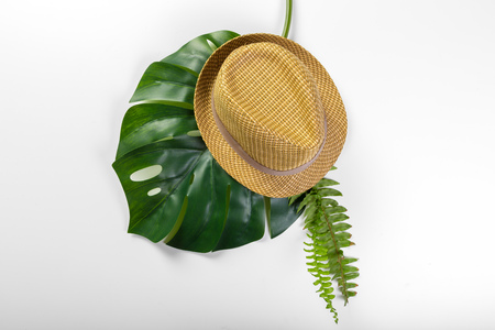 Monstera leaves and a hat
