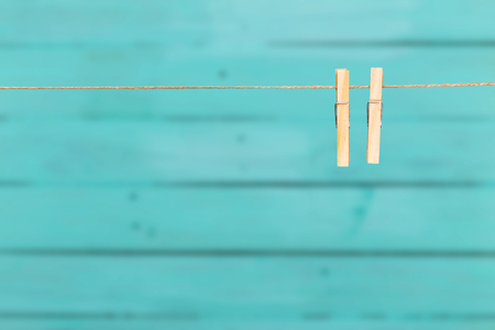two clothespins on rope over blue wooden background Archivio Fotografico