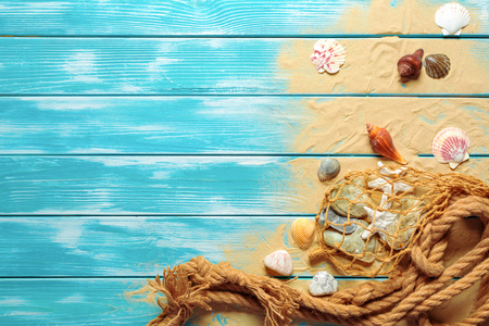 sea rope with many different sea shells on the sea sand on a blue wooden background. Top view Foto de archivo
