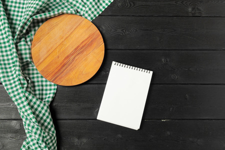 Blank sheet of opened notepad and kitchen utensils on  table with tablecloth, copy space Imagens