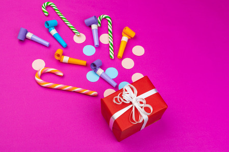Box with splashed confetti of ribbon, dudes and other festive accessories Imagens