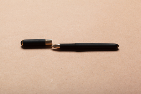 Black luxury ball point pen on beige background