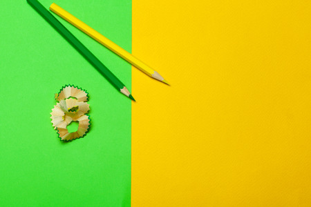 Shavings of pencils with paper on bright green background
