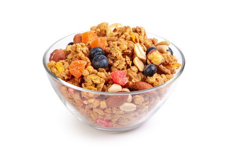 Bowl of homemade granola with fruit pieces isolated on white 免版税图像