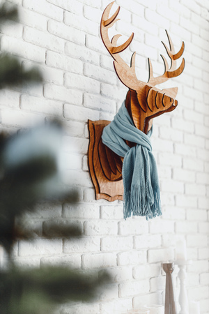 Decorative wooden Christmas elk with a scarf in interior 免版税图像