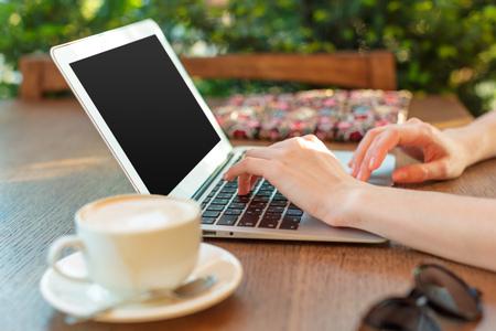 Femme utilisant un ordinateur portable pendant une pause-café
