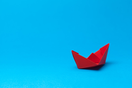 Origami paper boat on blue background