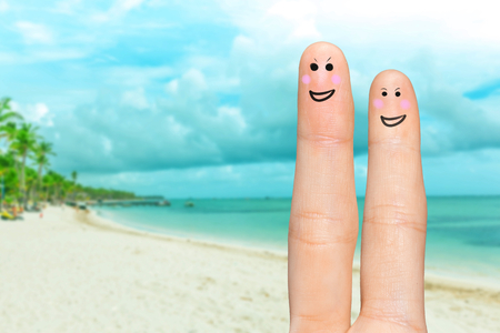 Human hand fingers with funny painted emoticons. People relationships concept