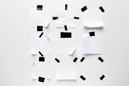 White ripped note, notebook paper stuck with black sticky tape isolated on white background. Creative Photo