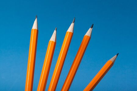 Bunch of orange pencils on blue background close up. Creative Photo