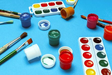 Art supplies. Watercolor paints and brushes on bright blue background. creative photo