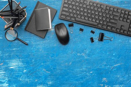 Composition of office supplies and equipment in black and blue colors, top view