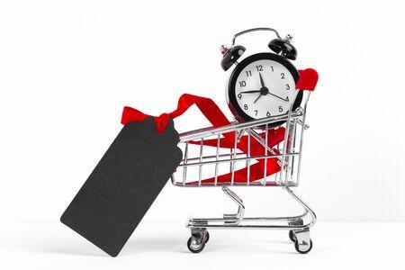 Small shopping cart with alarm clock. Shopping time concept. creative photo.