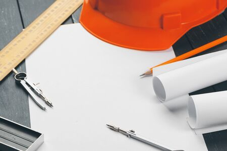 Engineer workplace with blueprints, compass, pencil and safety helmet Reklamní fotografie