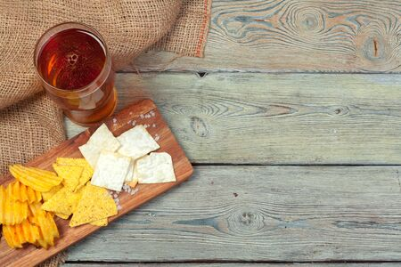 Lager beer and snacks on wooden table. creative photo. Zdjęcie Seryjne