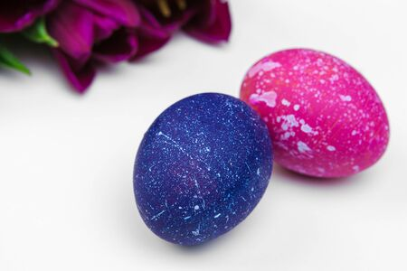Easter eggs with tulips flowers on white background. creative photo.