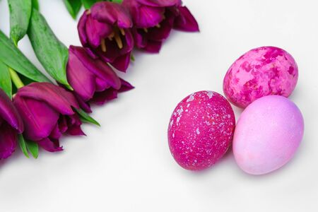 Easter eggs with tulips flowers on white background. Creative photo. Zdjęcie Seryjne