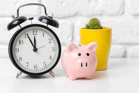 Piggy bank save coin and alarm clock, time and money concept.