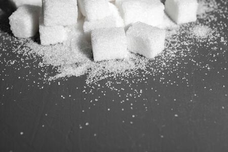 White sugar cubes over black background close up