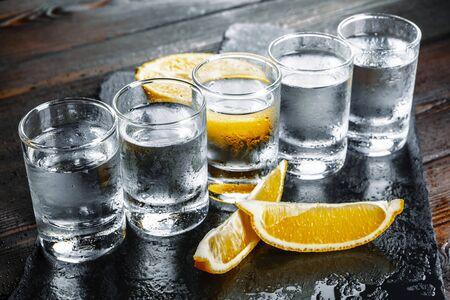 Vodka in shot glasses on rustic wood background. creative photo.