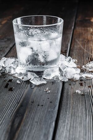 Vodka in shot glasses on rustic wood background. Creative photo.