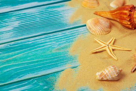 Sea sand and Sea shells on blue wooden floor. Creative photo.