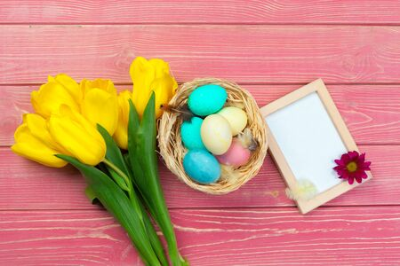 Easter concept. Wooden frame with easter eggs and tulips on colorful background. Creative photo. Фото со стока