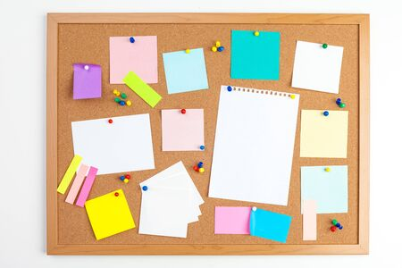 Cork board with several colorful blank notes with pins. creative photo.