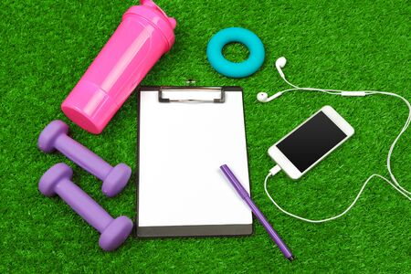 Sheet of paper and sports equipment on grass close-up. creative photo.