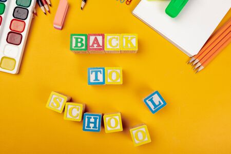Back to school concept. Colored wooden alphabetical cubes on bright yellow background. creative photo.