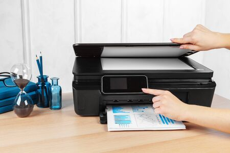 Unrecognizable young businesswoman making copies on the photocopy machine at the office