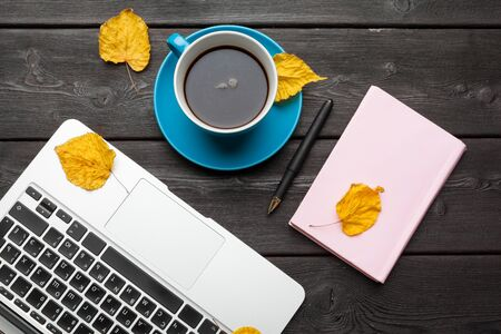 Office table with blank notebook and laptop Coffee cup