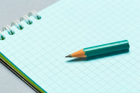 Short worn pencil with notepad on gray desk. creative photo