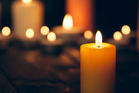 candles burning in darkness over black background. commemoration concept. Imagens