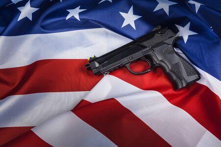 Handgun lying on American flag. Weapon problem concept Foto de archivo
