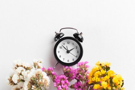 Spring Time Change Background with alarm clock and flower branches. creative photo.