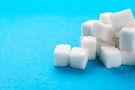 White sugar cubes on a bright blue background creative photo. Standard-Bild