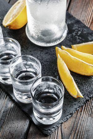 Vodka in shot glasses on rustic wood background creative photo.