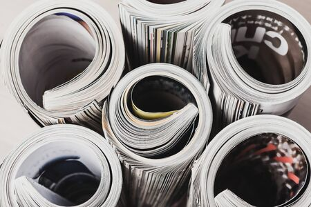 Glossy magazine with pages rolled. Creative photo.