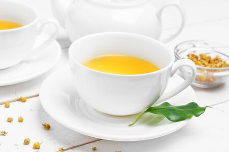 teapot and cups of tea on a white wooden background