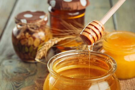 Honey background. Sweet honey in glass jar on wooden background. creative photo.