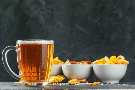 Lager beer and snacks on stone table. Cracker, chips side view. creative photo. 版權商用圖片 - 142084644