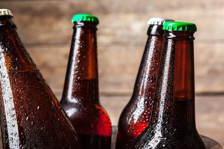 Cold bottles of beer in the bucket on the wooden background. creative photo.