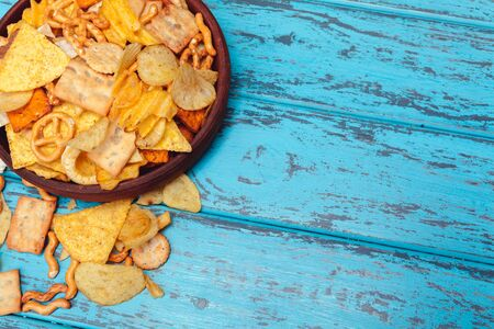Beer snacks like crackers, chips, cookies on a wooden surface