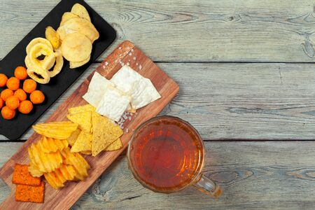 Lager beer and snacks on wooden table. 版權商用圖片 - 142086090