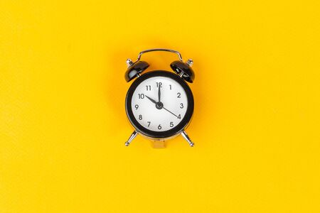 Alarm clock on bright yellow background close up