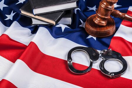 Gavel, handcuffs and american flag on wooden background.